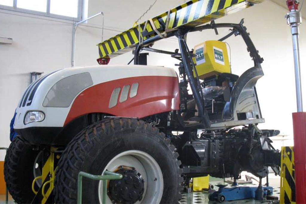 Die Abbildung zeigt eine Traktorfahrerkabine beim ROPS Test an FJ-BLT Wieselburg bei der Aufbringung der Vertikallast. Der Traktor wird entsprechend OECD Code 4 gepüft. Deutlich zu erkennen ist die Verformung der Traktorfahrerkabine durch die Prüflast un....